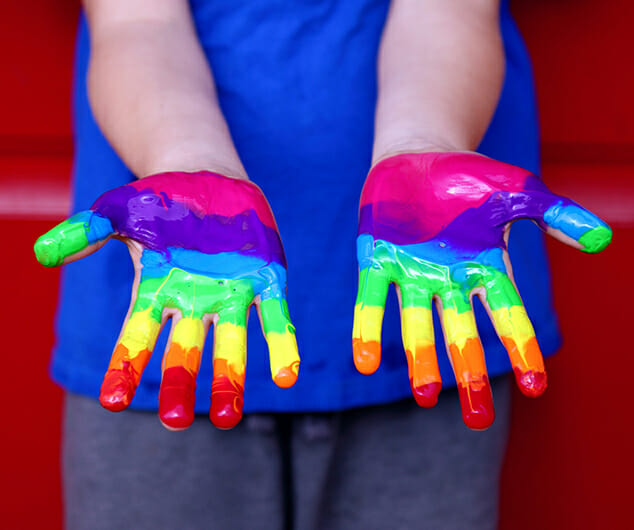Person's hands covered in LGBTQ rainbow paint