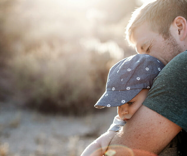 A young dad hugs his infant child